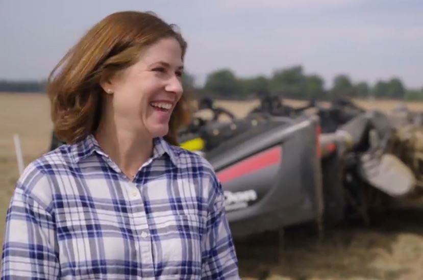 Rice farmer Jennifer James stands in rice field in front of tractor, smiling, brown hair blowing in the wind, wearing blue & white plaid shirt