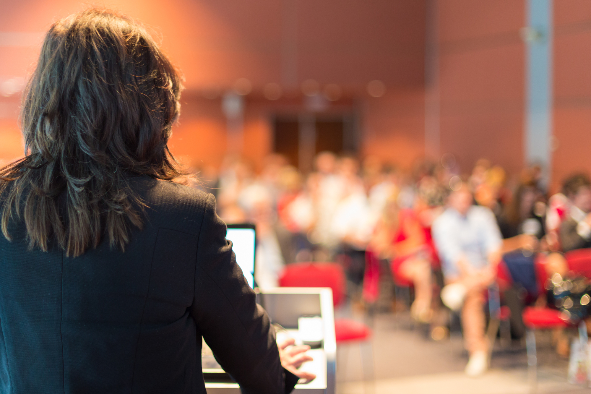 Dark-haired woman with her back to the camera stands at podium facing blurry crowd of people sitting in red chairs