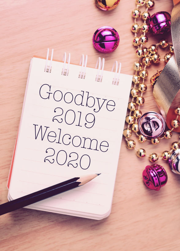 """Goodbye 2019 Welcome 2020 written on memo pad surrounded by glittery buttons and beads"