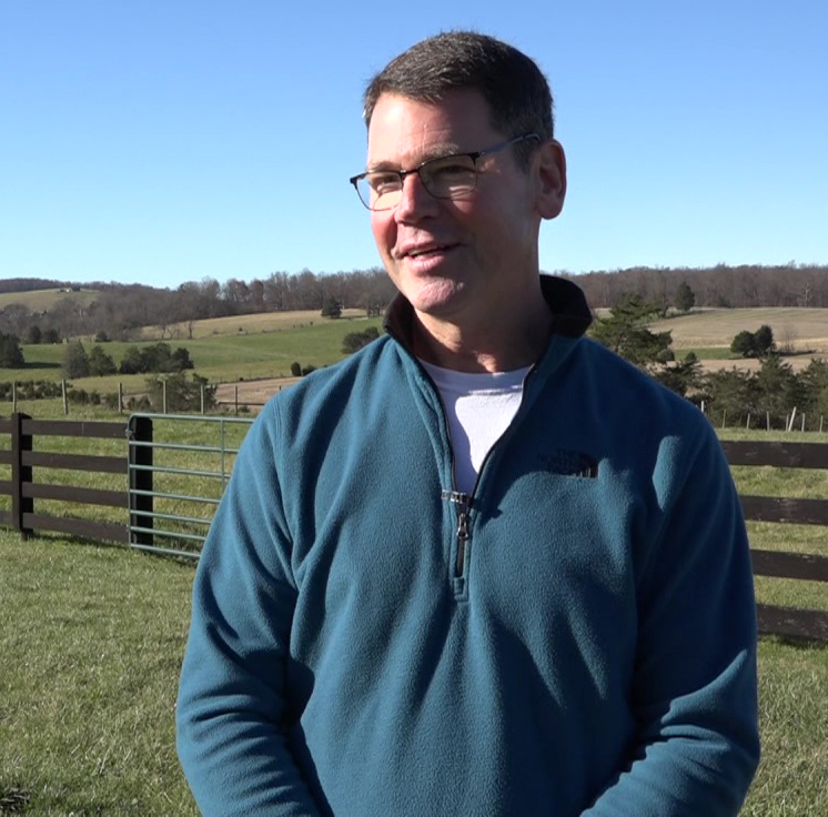 White man wearing glasses & blue sweater standing in fenced in field among rolling hills