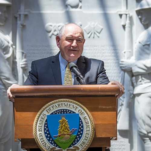 Secy Sonny Perdue stands at podium adorned with the USDA seal