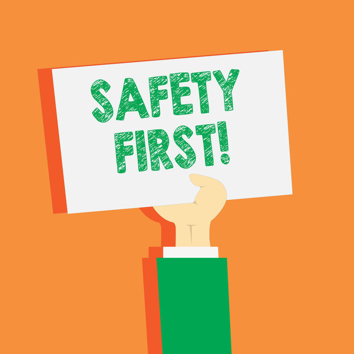 Graphic of hand holding Stay Safe sign on orange background