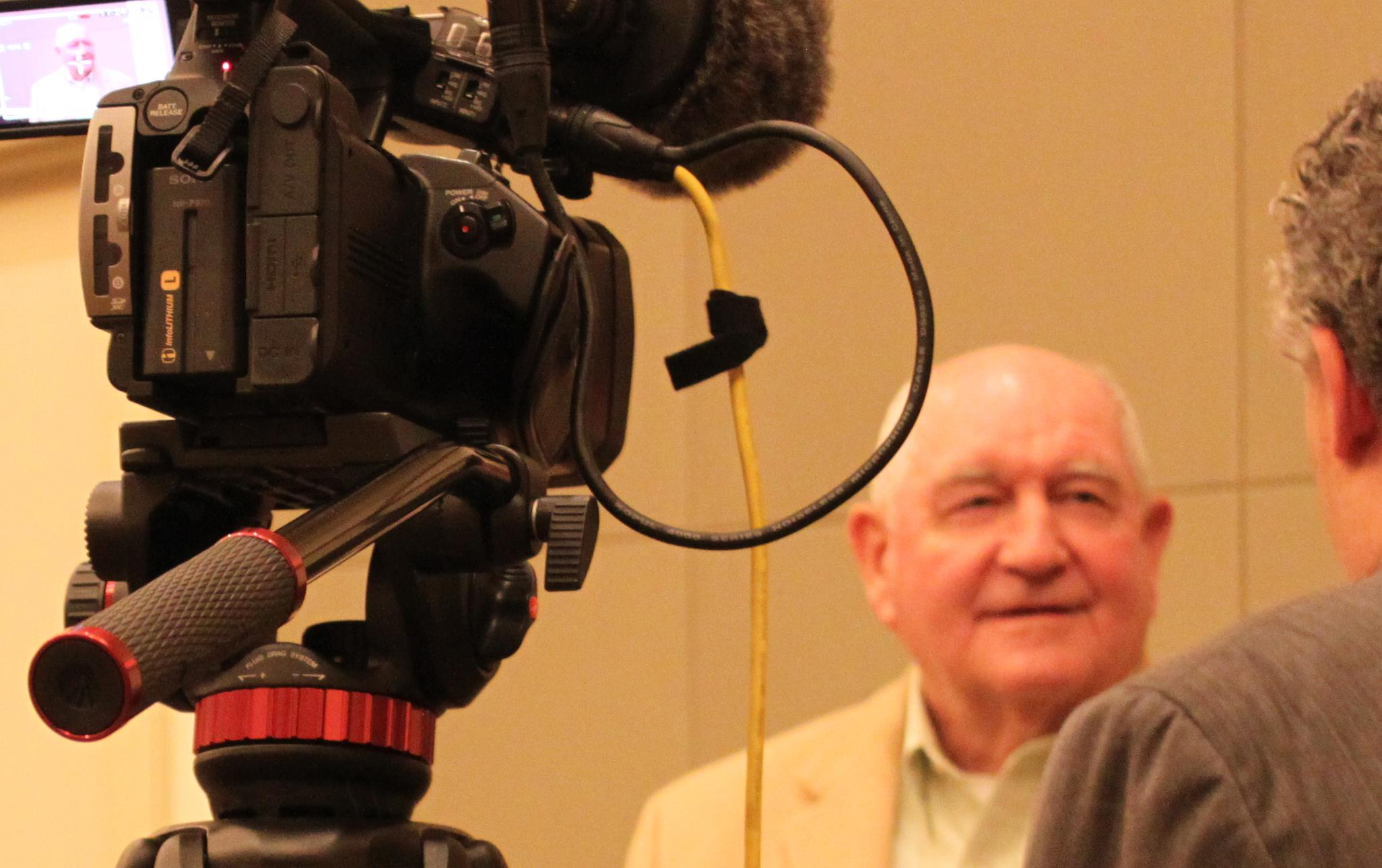 Bald white man stands in front of video camera being interviewed by man wearing a suit