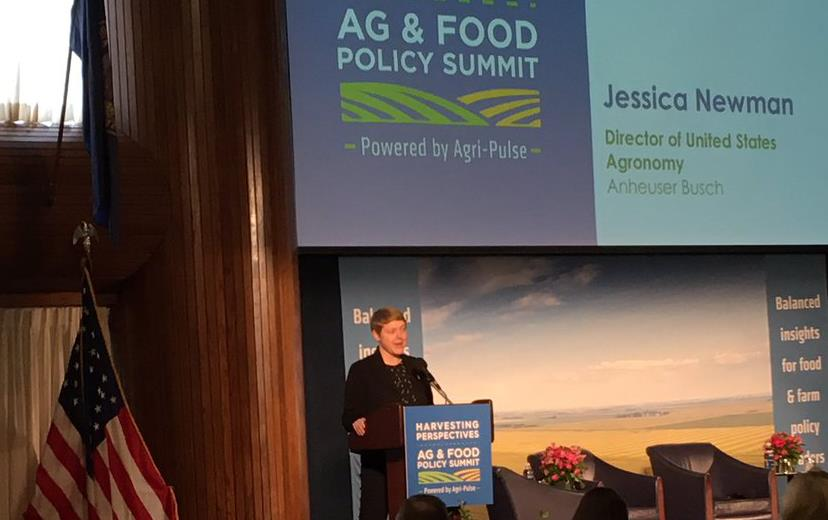 "Woman at podium, American flag to the left, under banner text ""Harvesting Perspectives Ag & Good Policy Summit"""