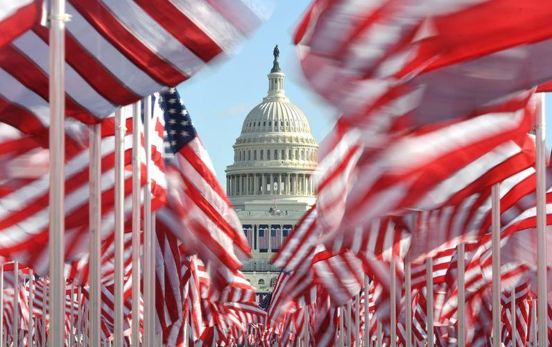 Field of waving American flags framing US Capitol dome