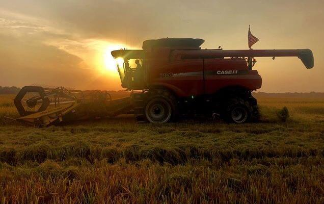 Combine at sunset with American flag flying from back