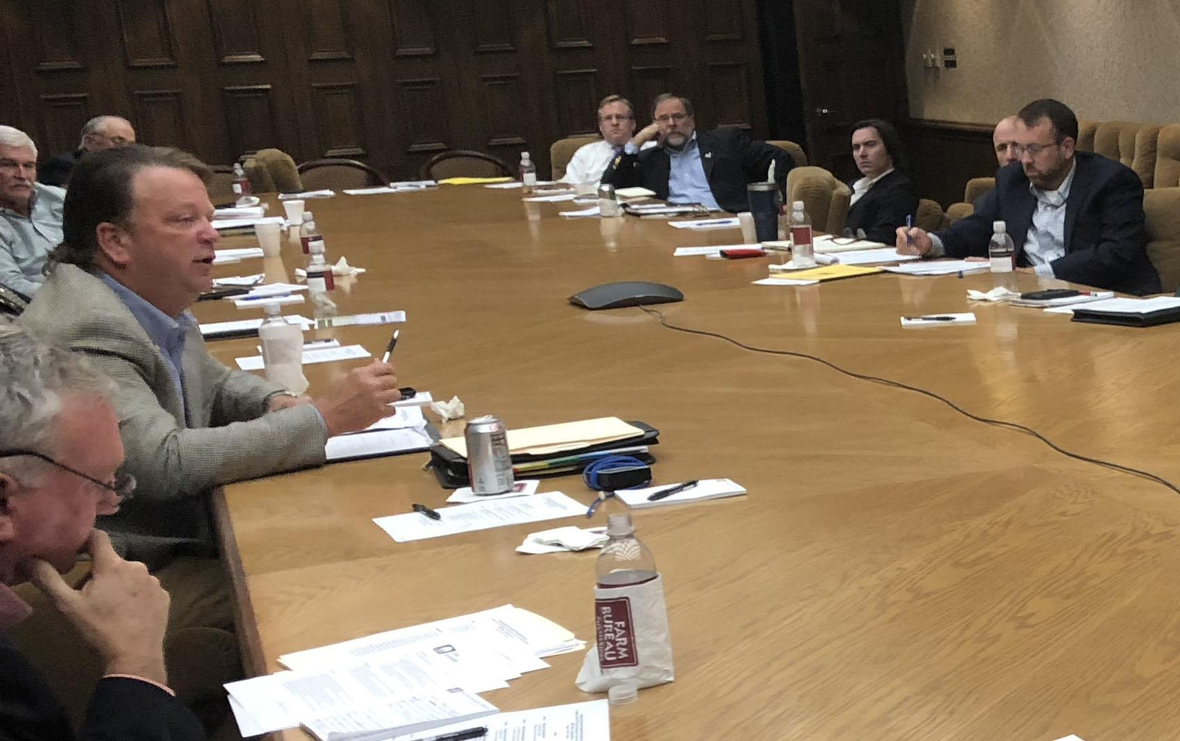 FDA round table discussion in Mississippi, group seated around large wooden table covered with papers