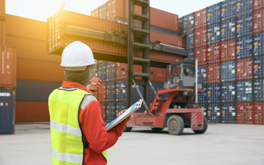 Foreman wearing safety vest, holding clipboard and cellphone, stands in front of forklift moving shipping containers