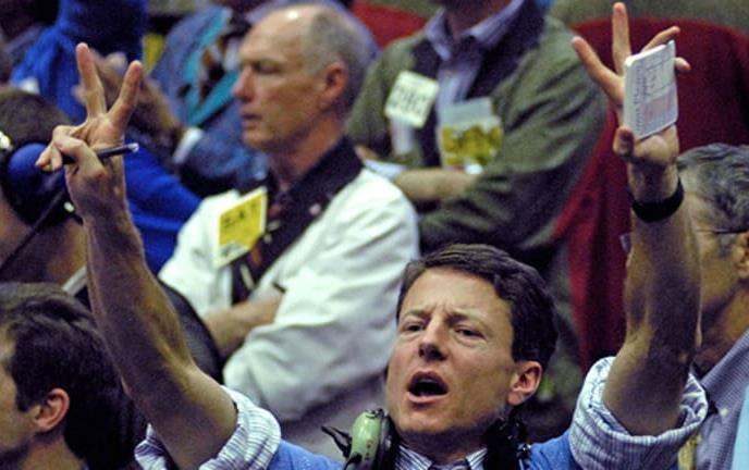 Crowd of traders on stock market floor, man in foreground has both arms raised and is shouting
