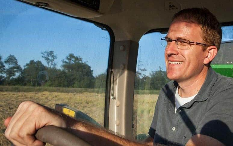 Smiling farmer in combine cab with hands on the steering wheel
