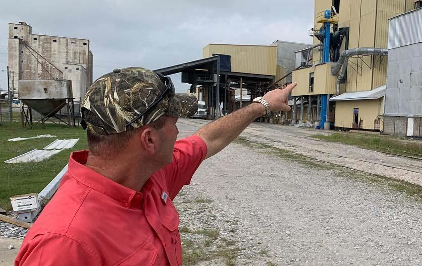 Man wearing camo ballcap points to rice milling facility
