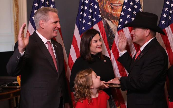 Rep Troy Nehls swearing ceremony shows two men in dark business suits, raising their right hands, surrounded by woman and three girls, everyone stands in front of American flags