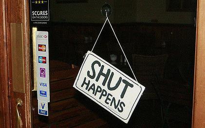 """Sign on glass door of business saying """"Shut Happens"""""""