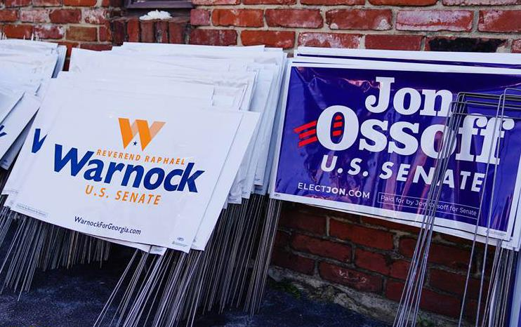 Campaign signs for Raphael Warnock and Jon Ossoff stacked against a brick wall