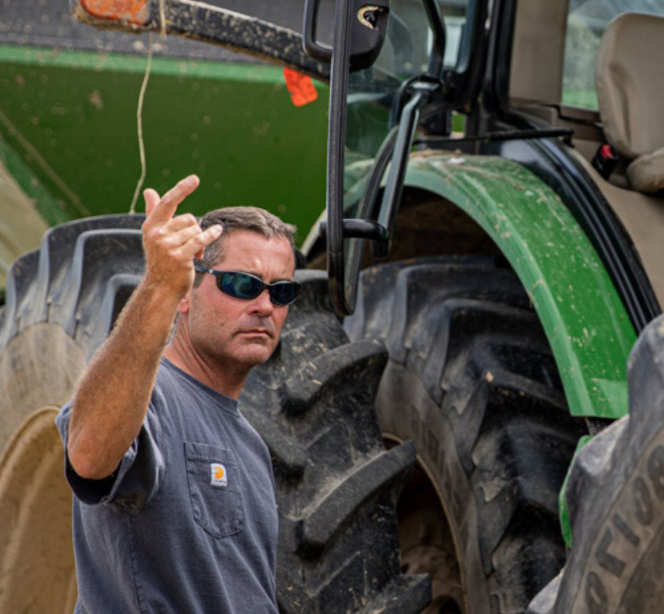 White man wearing gray t-shirt and sunglasses stands next to large combine tires
