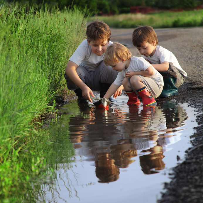 Children play with homemade sailboat in puddle next to overgrown, green, grassy area