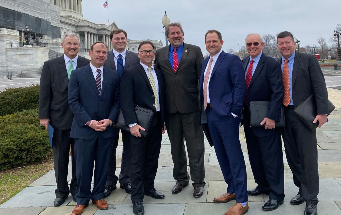 Group of business men stand on sidewalk outside US Capitol