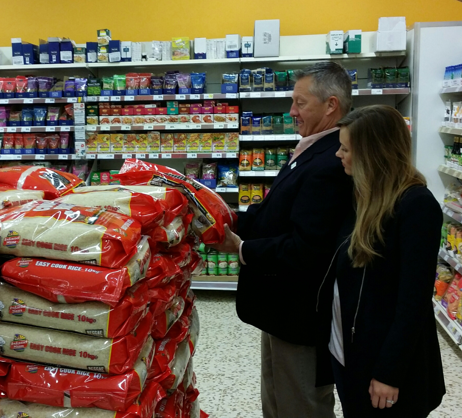 Man and woman in grocery store look at large bags of rice stacked in the aisle