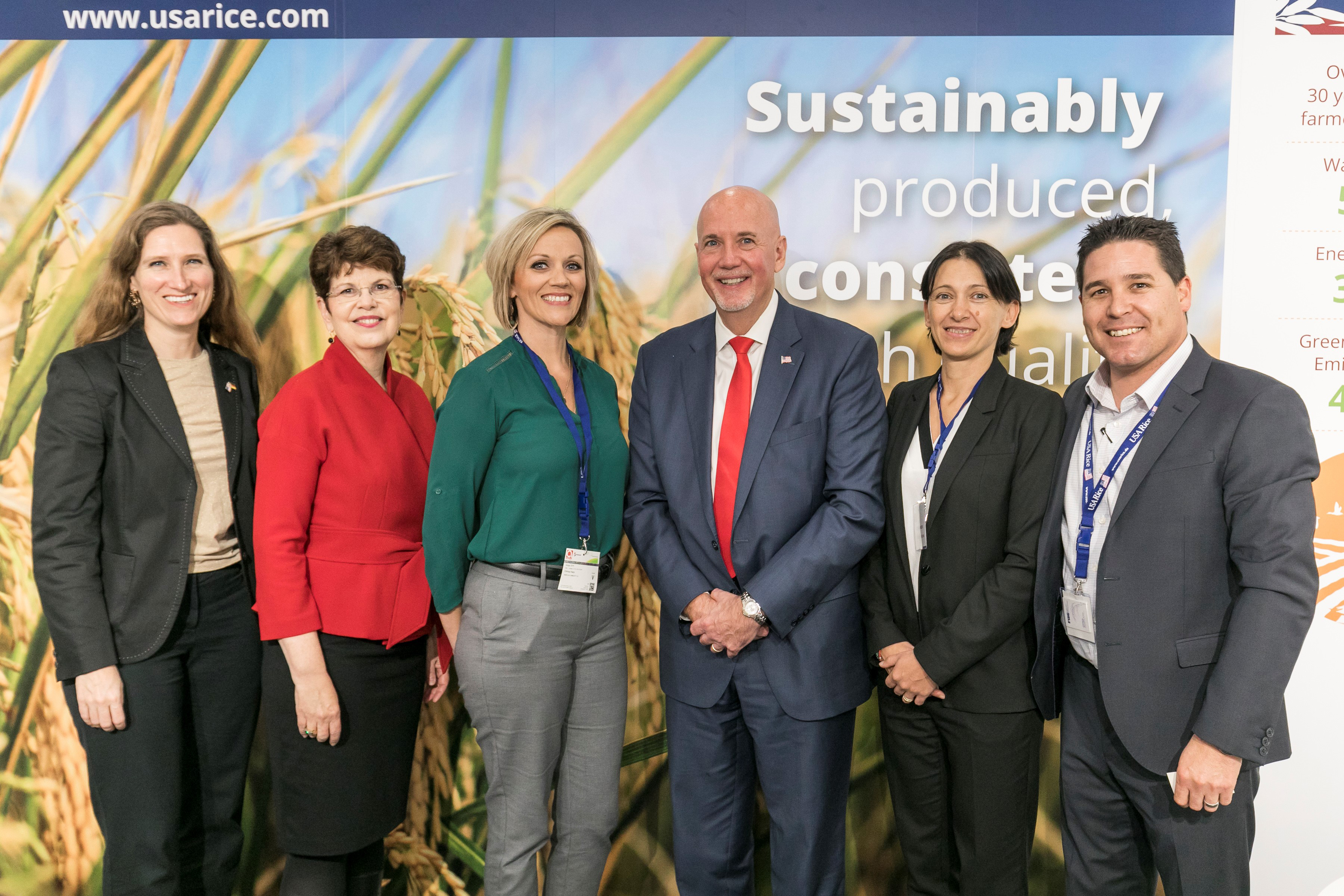 Group shot of people wearing business attire standing in front a poster of rice in the field with sustainability messaging, Kolnmesse photo