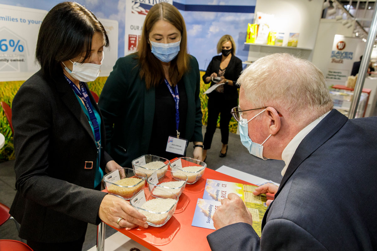 Anuga-USA-Rice-Booth, two women show man samples of rice, everyone is wearing face masks