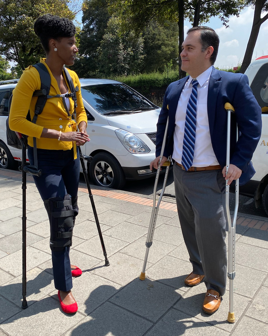A woman and man, both on crutches, stand on sidewalk talking