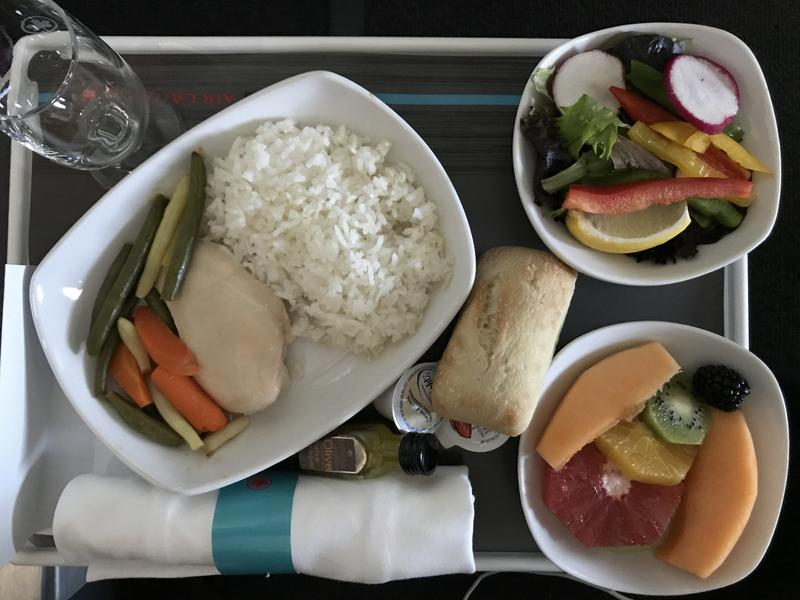 Airline food displayed in small white containers on tray including white rice, colorful fruit and vegetable salads, bread roll, and napkin