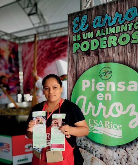 "Woman wearing red apron holds recipe cards in both hands, standing in front of promotional banner that says ""Piensa en Arroz"""
