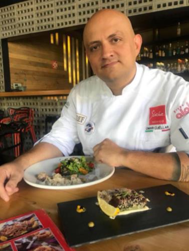 Chef Omar Cuellar, bald-pated man in chef