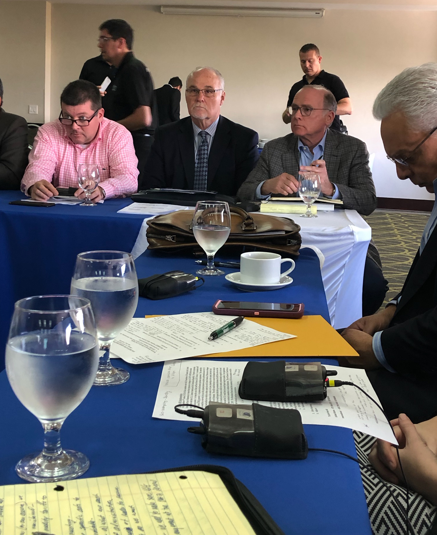 2019 Fecarroz mtg - people seated at table covered with blue tablecloth, glasses of water, paper, pens, and electronic devices