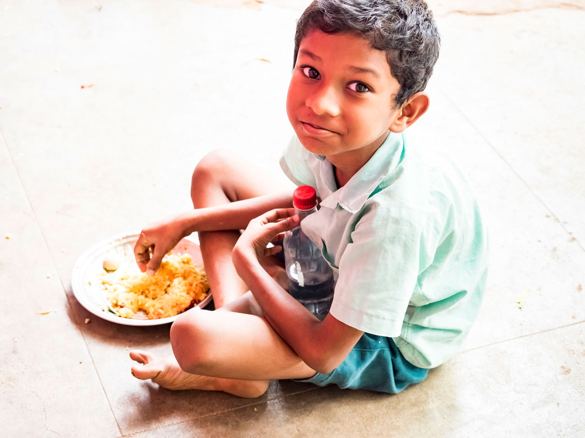 Young-boy-sitting-on-ground-eating-rice