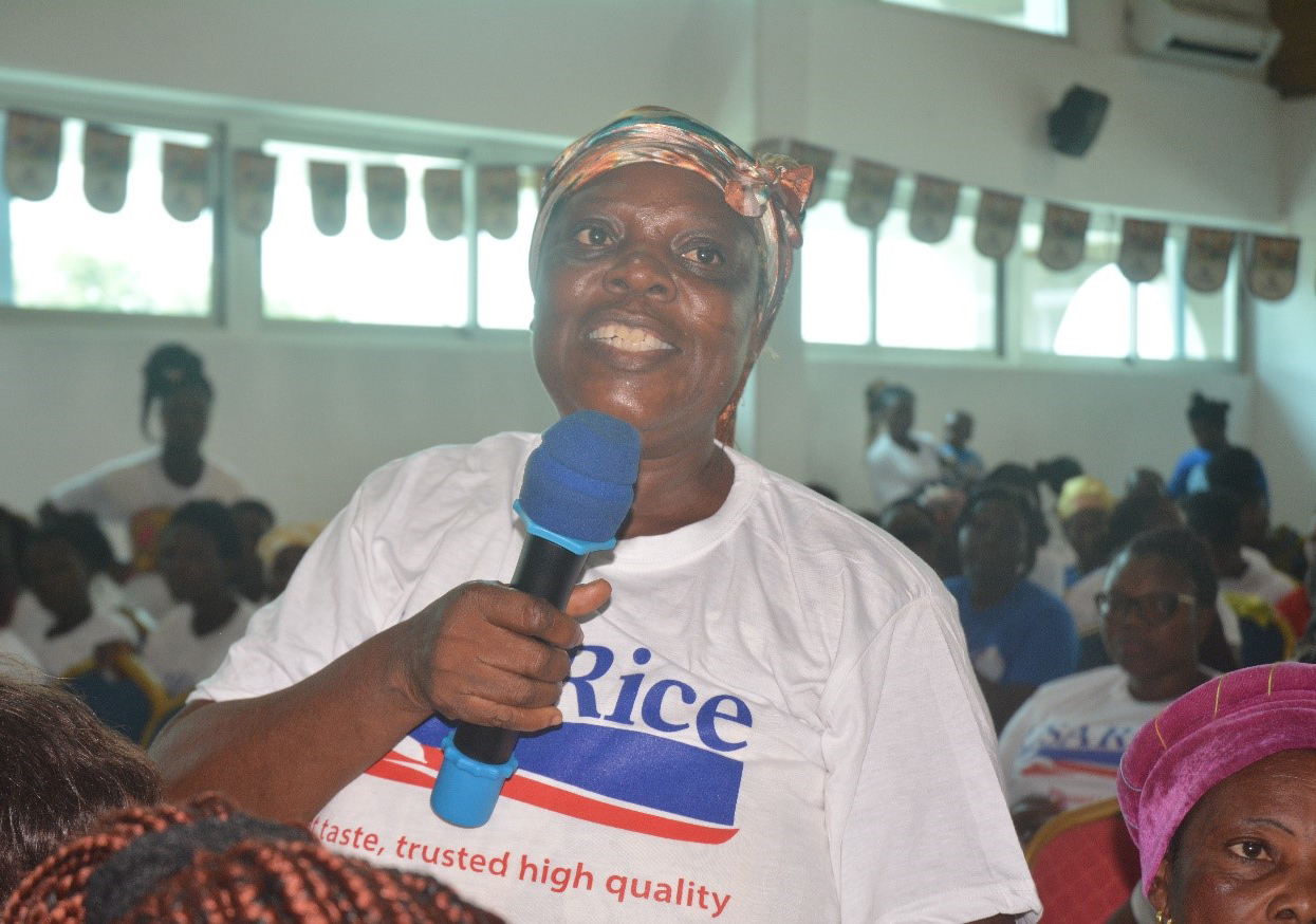 African woman, wearing white t-shirt with USA Rice logo, speaks into blue microphone