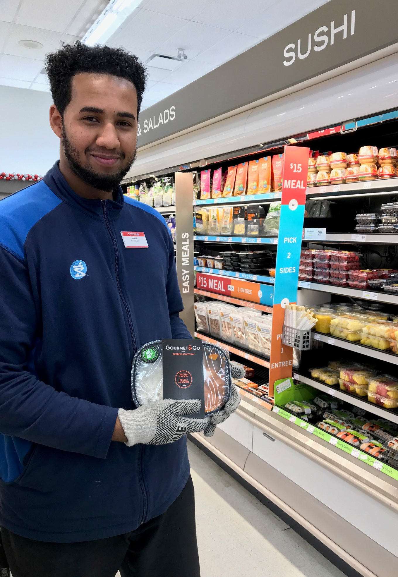 Young man wearing gloves, stocking shelves in grocery store holds Gourmet & Go butter chicken package