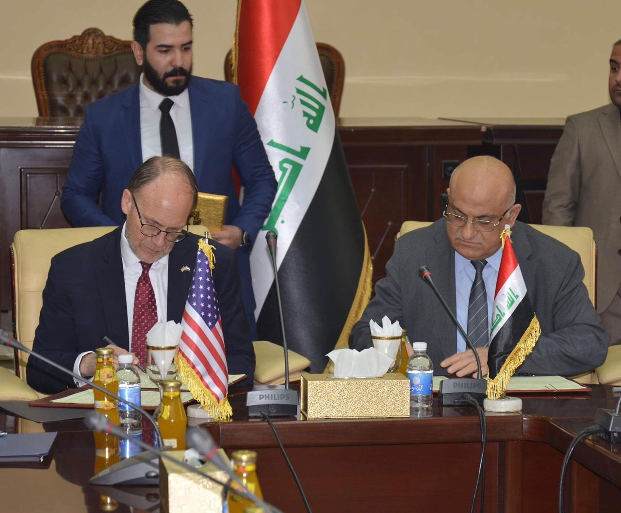 Two men sit at desk signing documents, US and Iraq flags in background