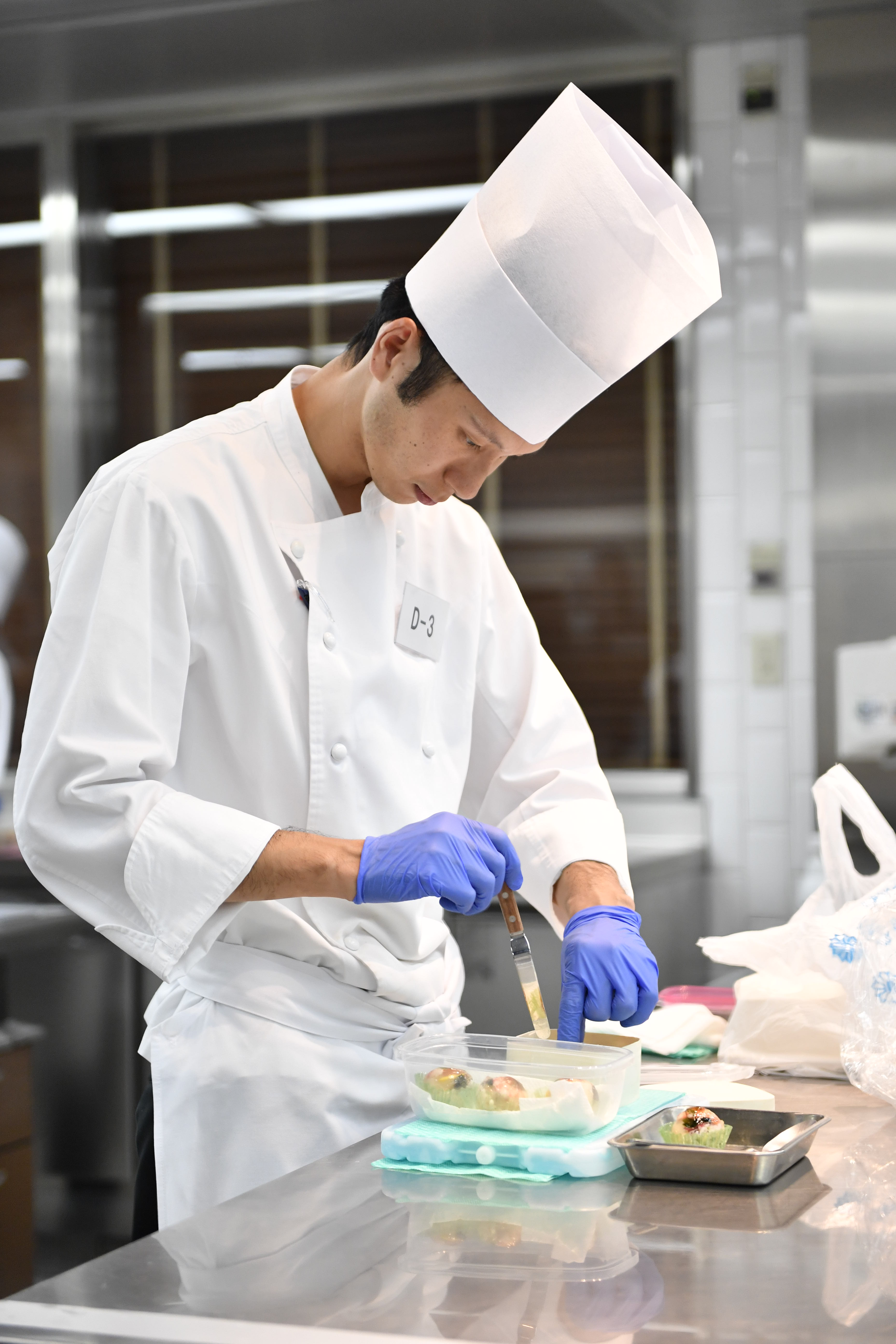 Man wearing white chef coat & hat and purple gloves holds knife while making sushi dish