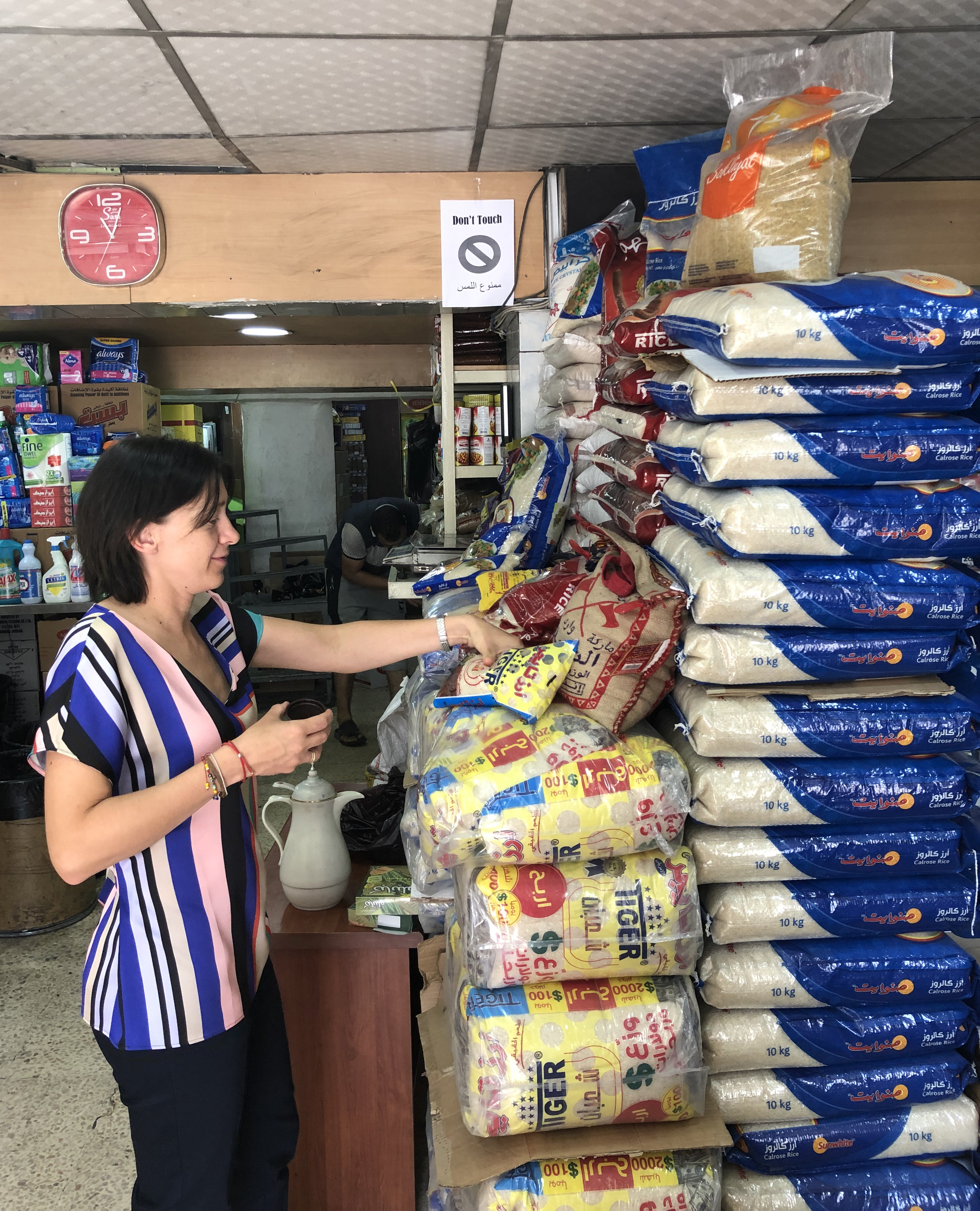 Woman wearing brightly striped shirt inspects rice brands in plastic bags, piled up to the ceiling