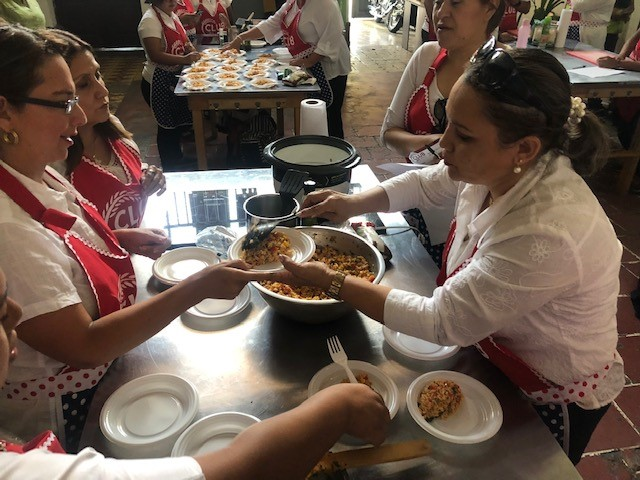 "Women wearing red aprons with text ""Club Arroz"" dish out rice samples for taste testing"