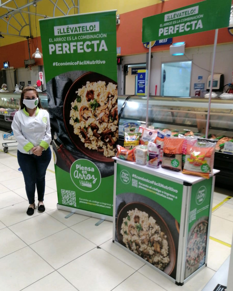 Piensa-en-Arroz-in-store-promotion booth with colorful photos of rice dishes and sample of rice on table