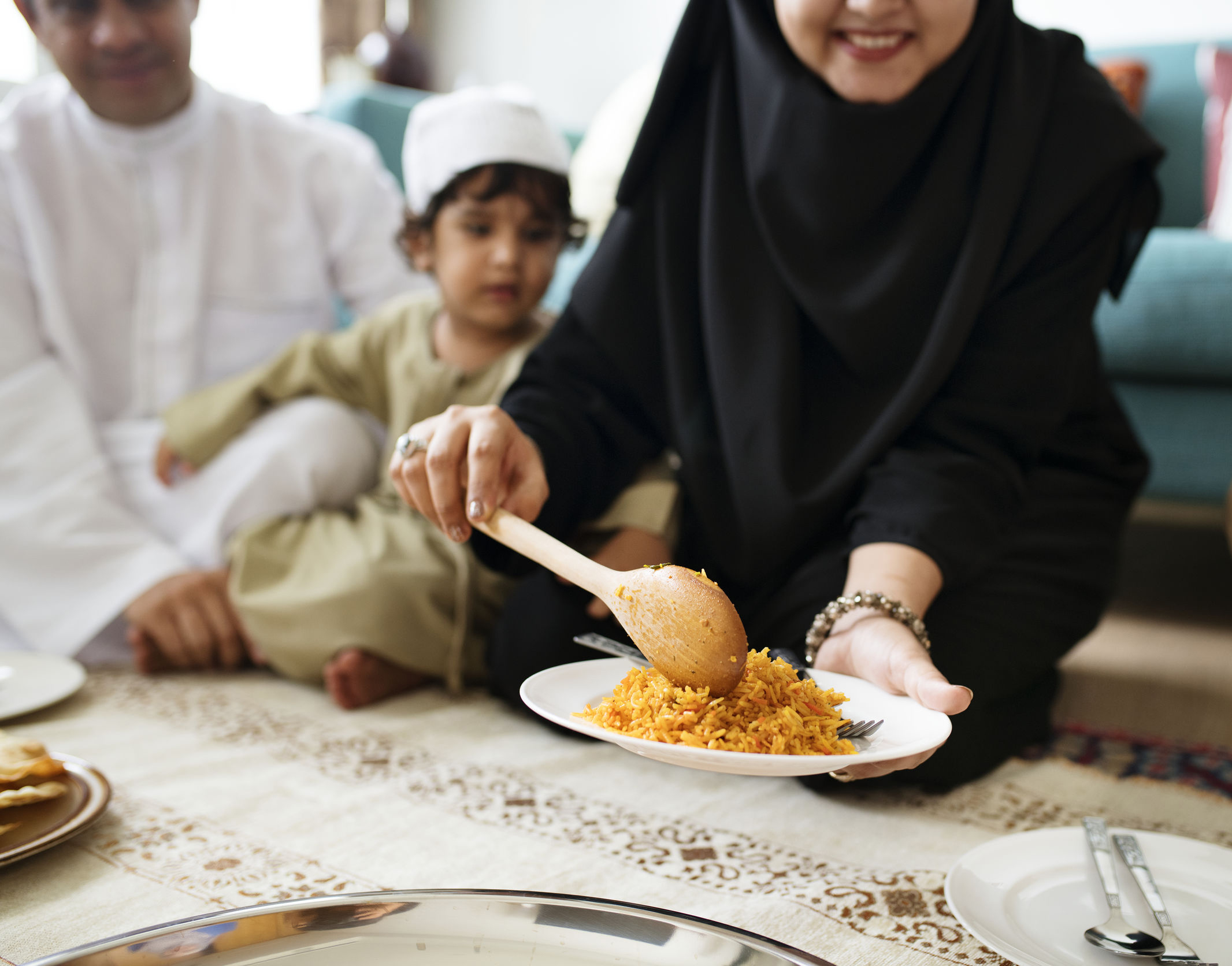 Woman offers plate filled with rice as man and young child look on