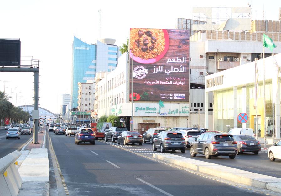 Saudi street scene with traffic driving under USA Rice billboard
