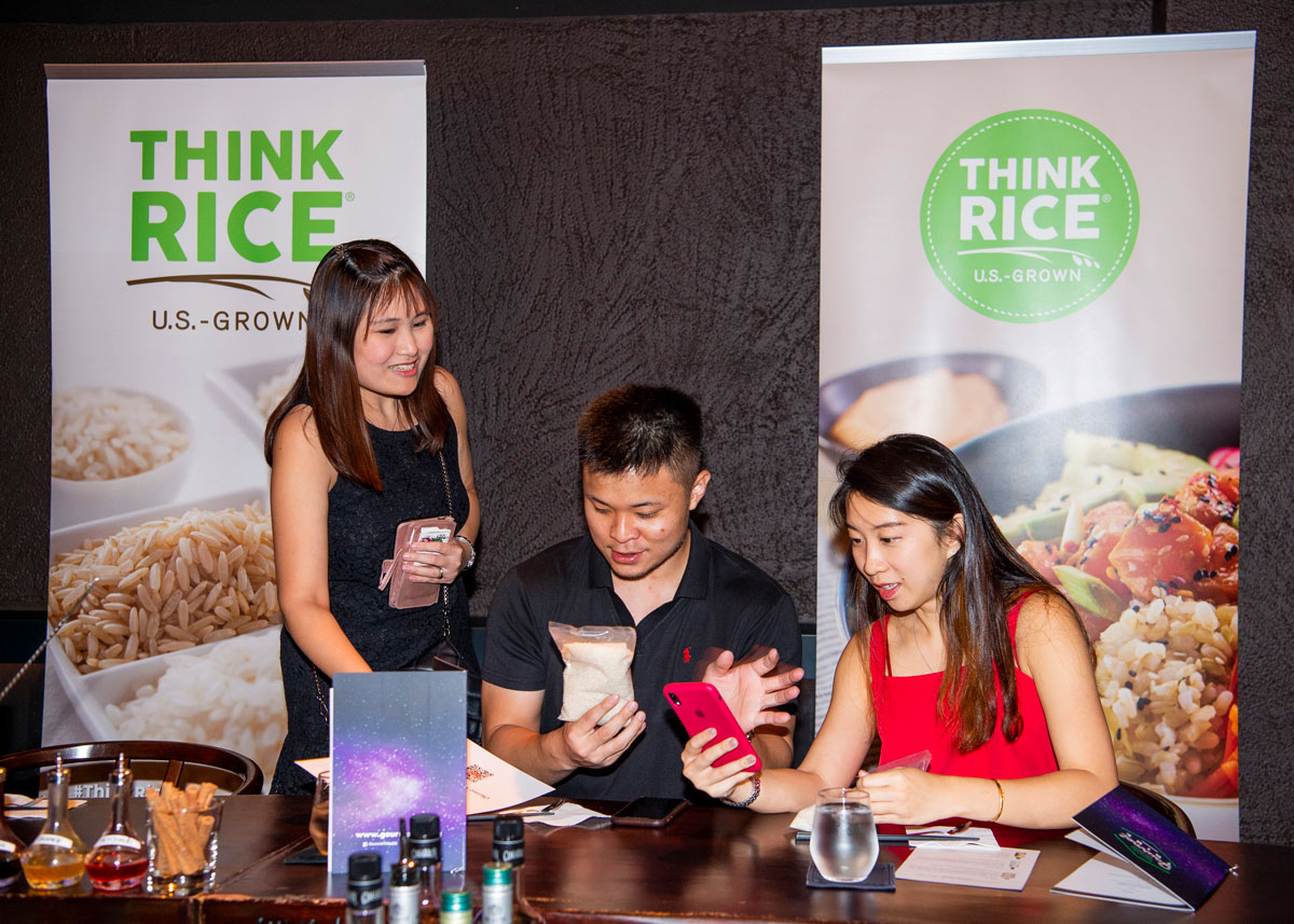 Three young Asian people use smartphones to take photos of rice samples; in background are two large posters with photos of rice dishes and Think Rice logos