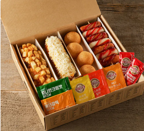 Box of corn dogs with packets of sauce