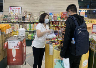 Woman and man, both wearing face masks, in discussion in grocery store