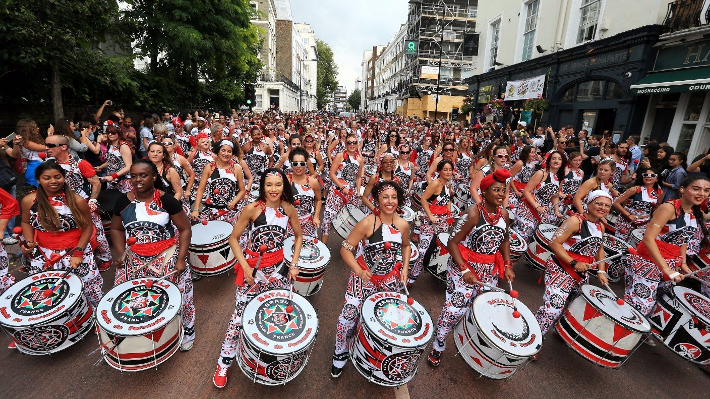 UK Street Festival, large crowd of drumers parade down the street dressed in black, red & white