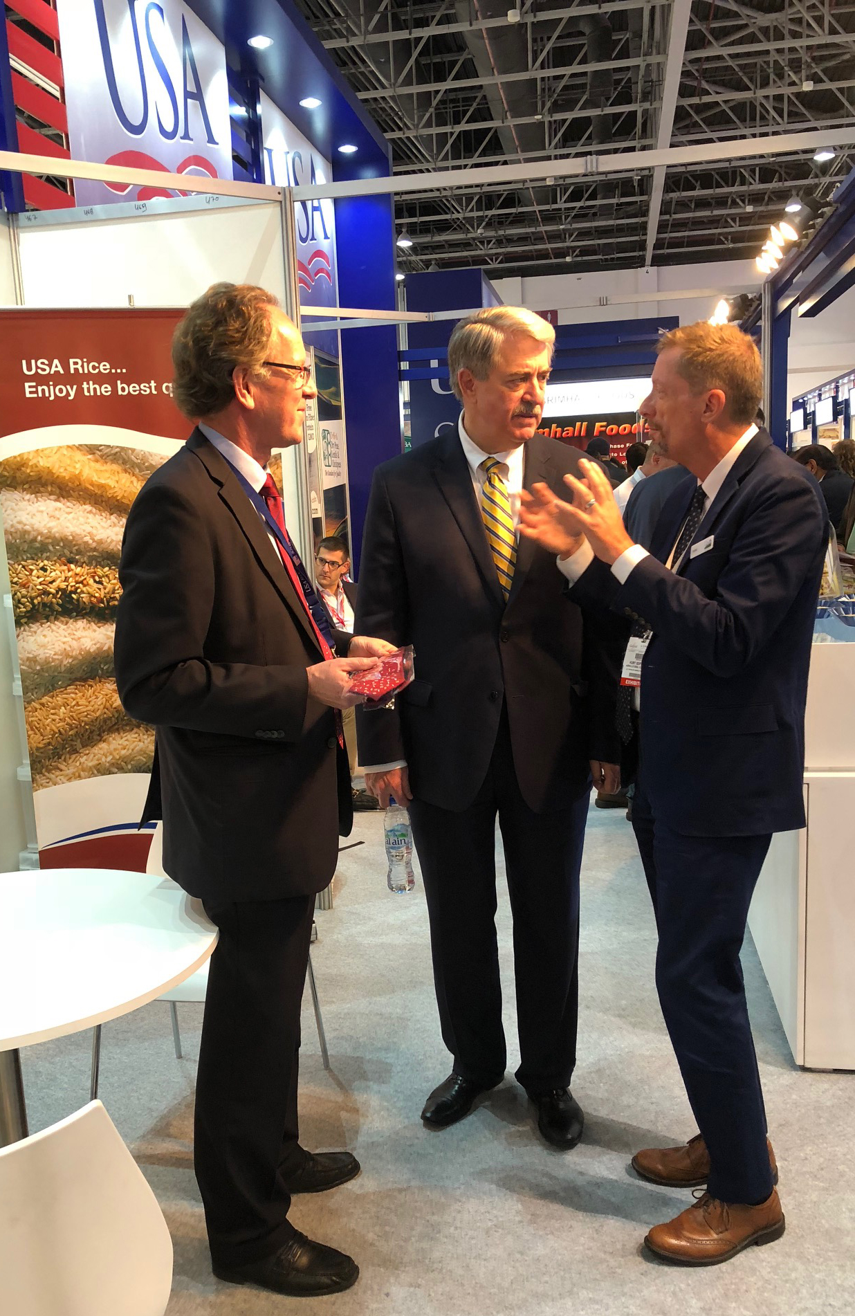 Undersecretary McKinney at USA Rice booth at Gulfood Show 2018 [image description: three men standing together talking in exhibit hall]