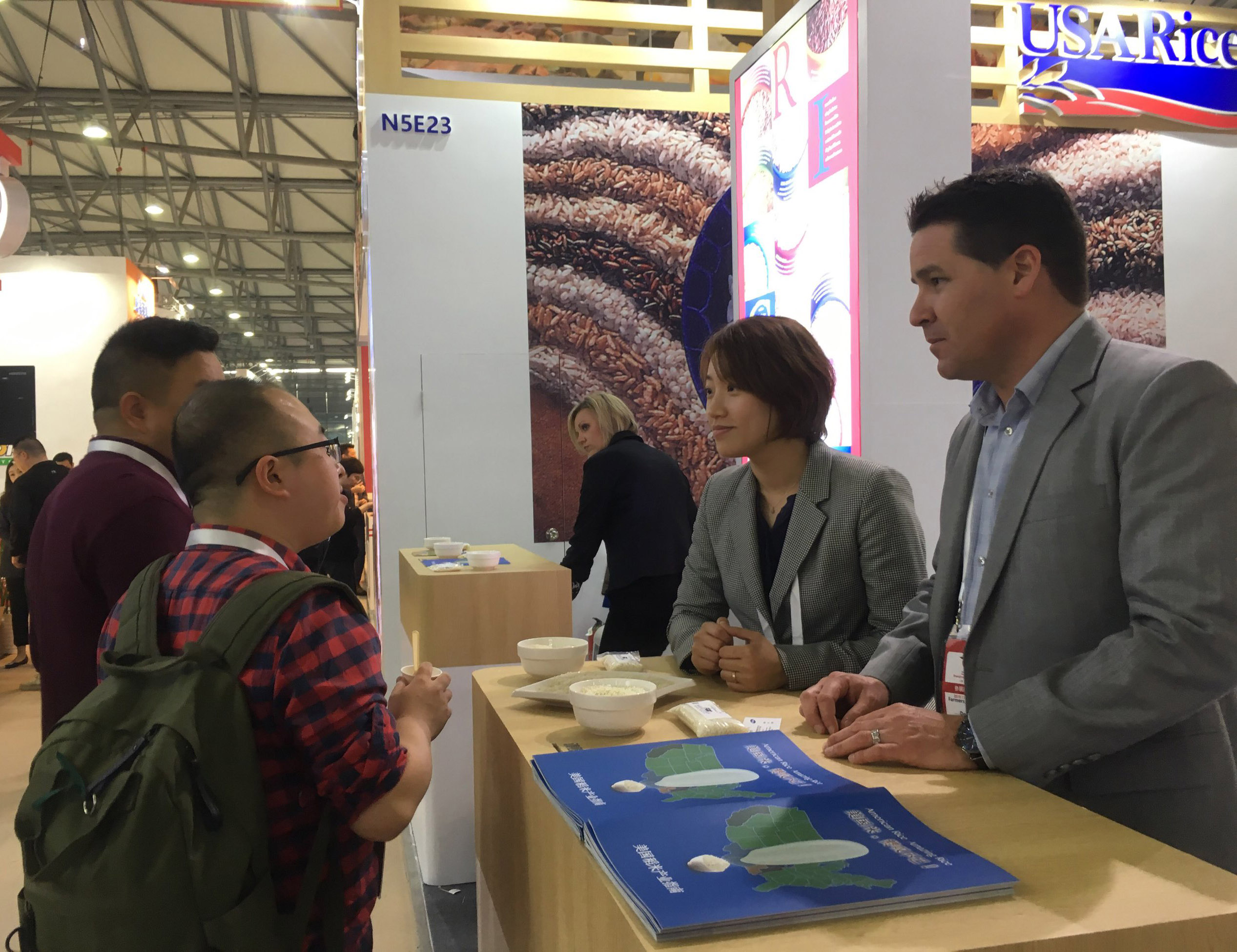 People gather at a trade show booth, standing around a table filled with rice bowls and pamphlets