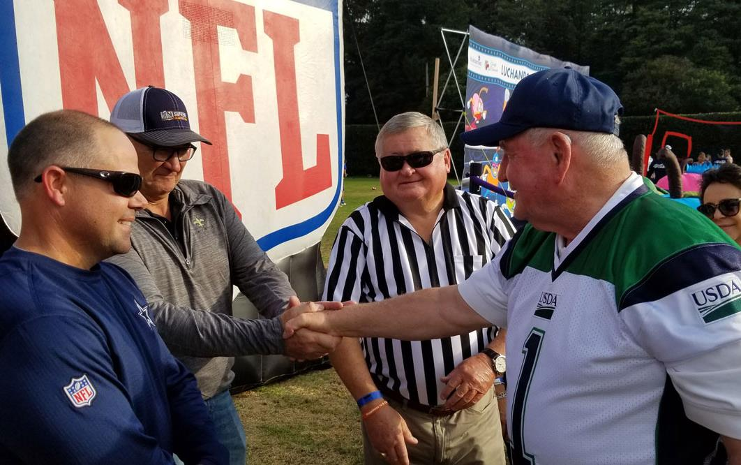 Men dressed in football jerseys shake hands in front of large NFL sign