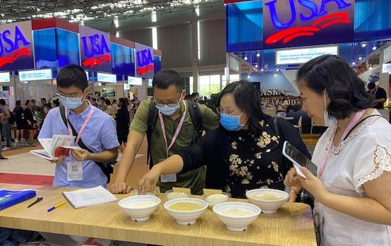 People wearing face masks stand around table filled with rice samples in white bowls