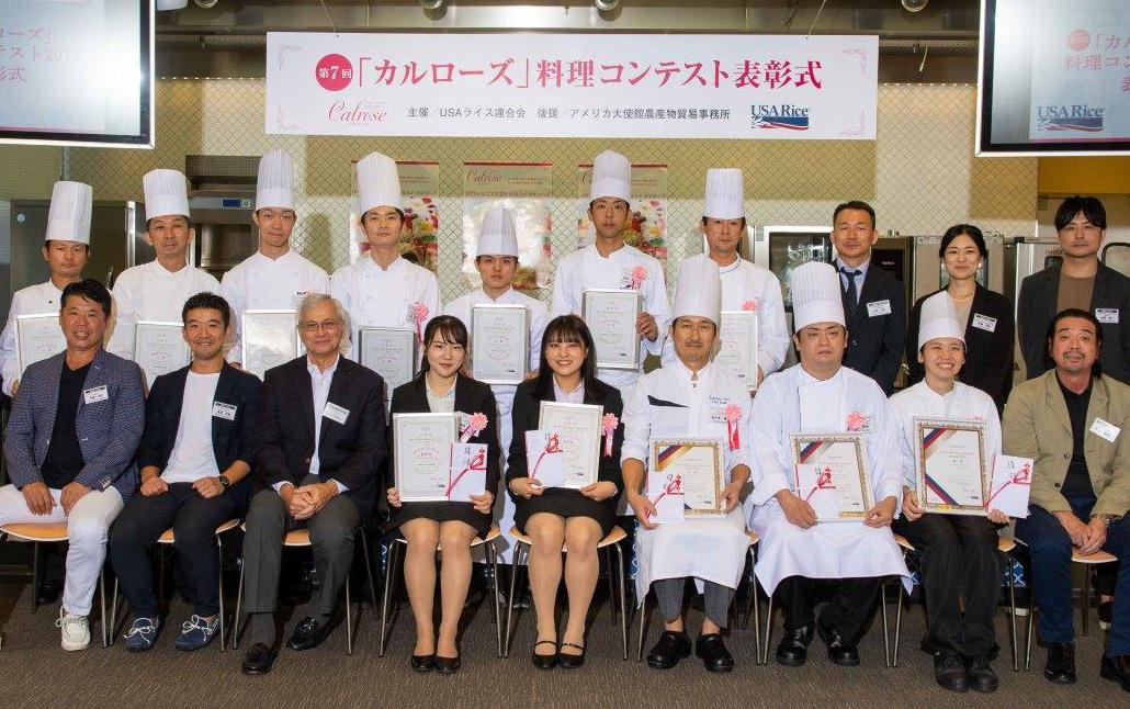 Group shot of chefs wearing toques and other people wearing business attire