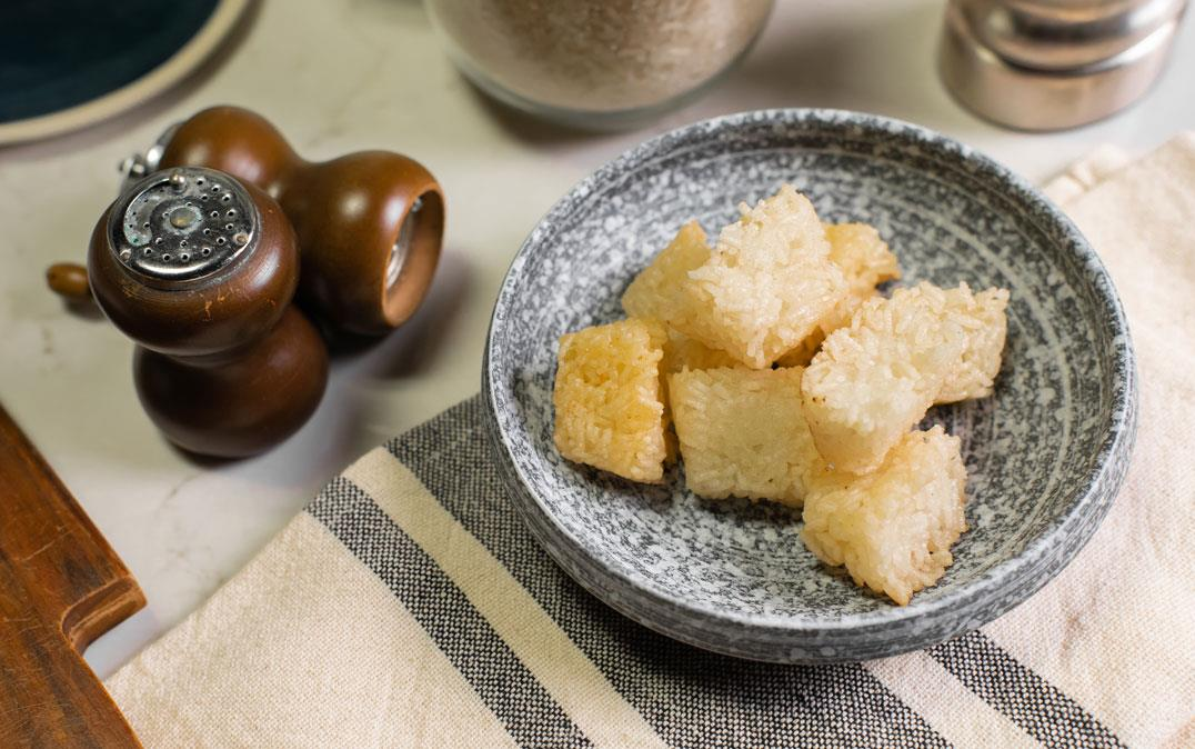 Rice croutons in bowl next to salt & pepper shakers