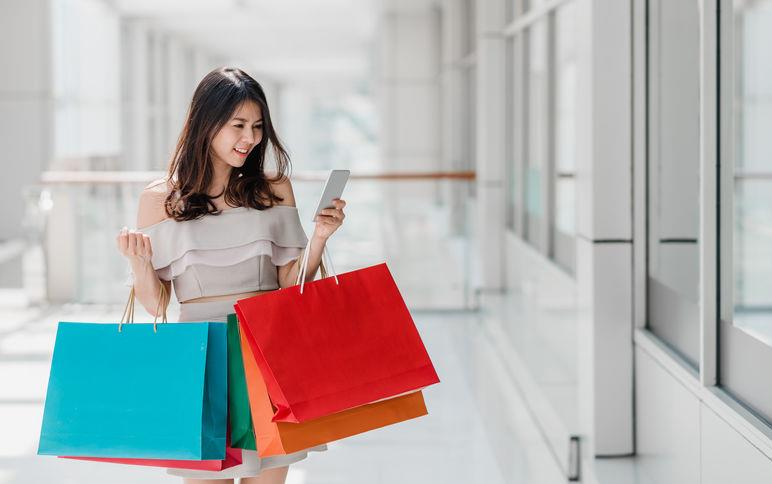 Young Asian woman walking in a mall holds multiple, colorful shopping bags and a cellphone